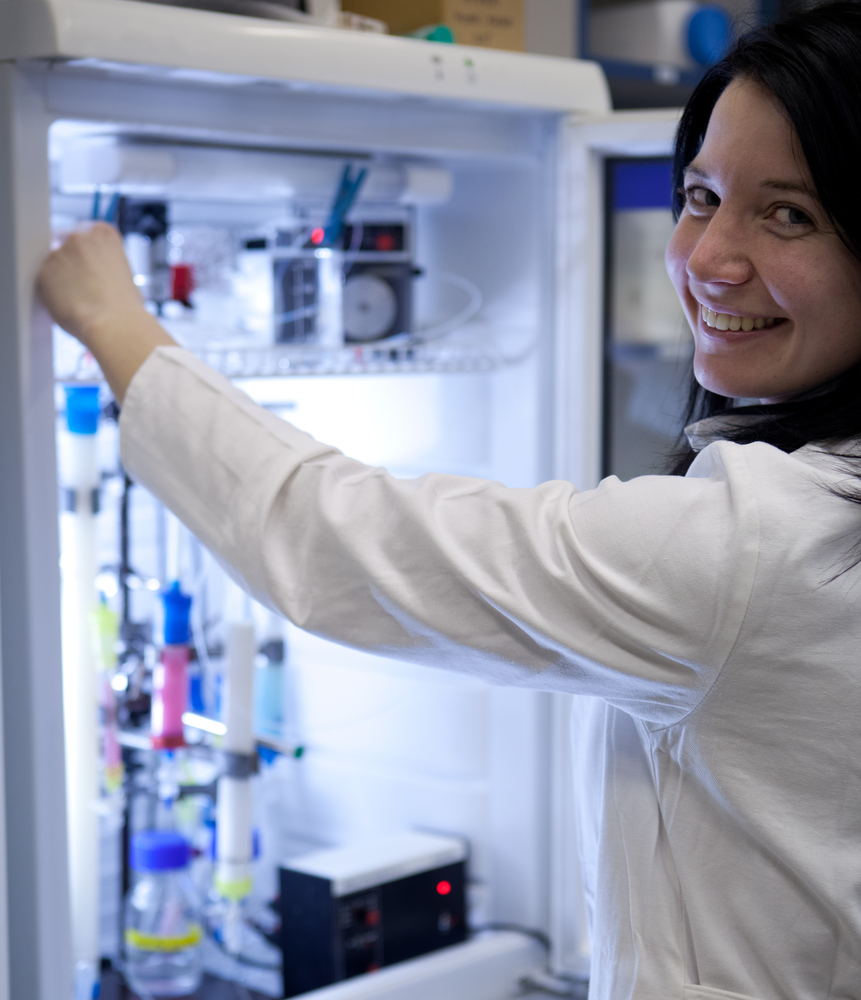 Portrait of a female researcher researcher taking a substance from a freezer