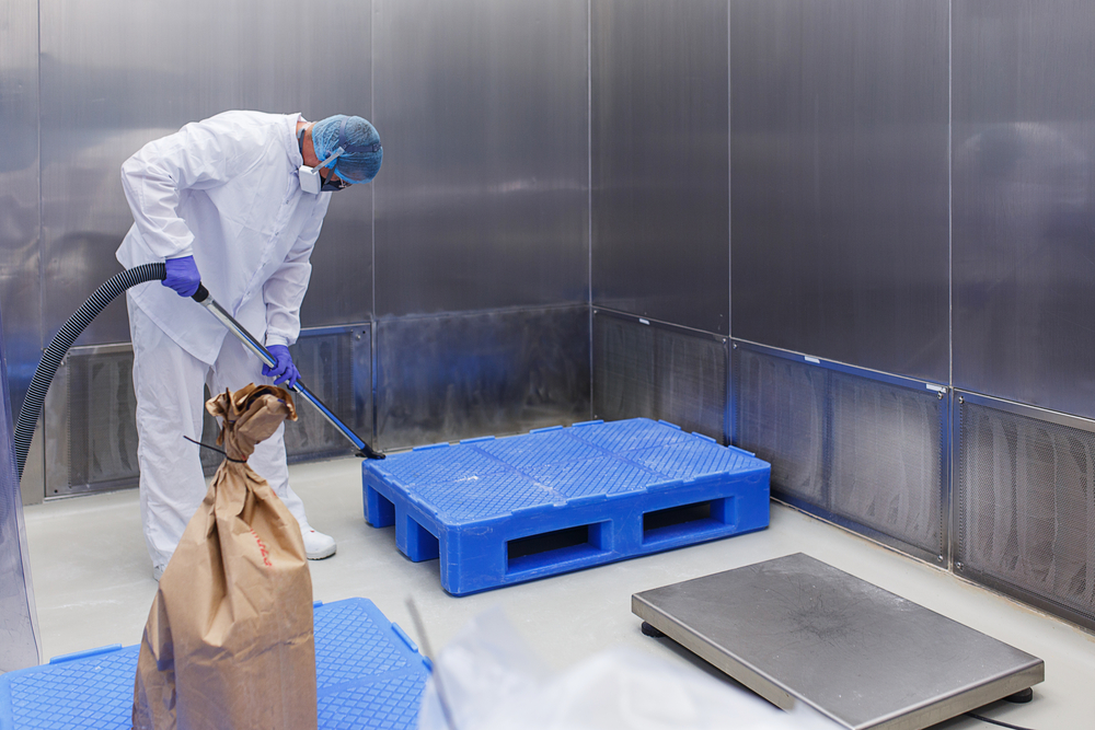 Production room in the medical laboratory. A specialist in protective clothing and a mask makes cleaning of a sterile room.
