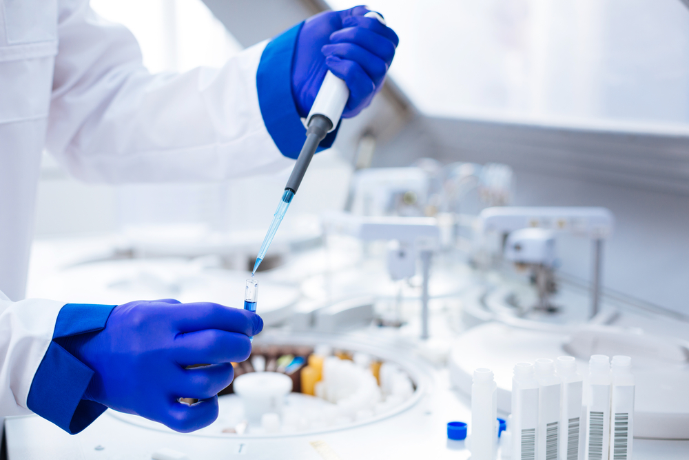 Hands in blue gloves holding pipette and test tube with poured blue chemical which placed on blurred background